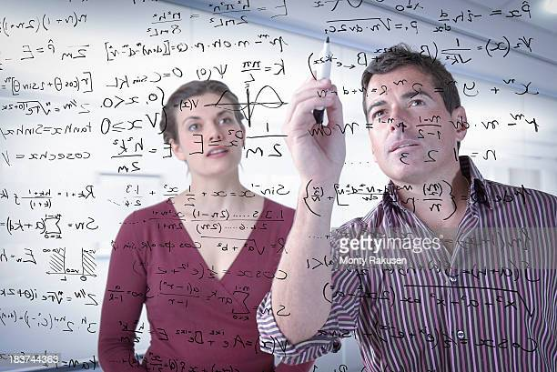 Mathematicians writing complex scientific equations on screen