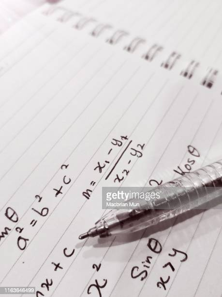 mathematics formula and symbols handwritten on notepad in black and white - physics stock pictures, royalty-free photos & images