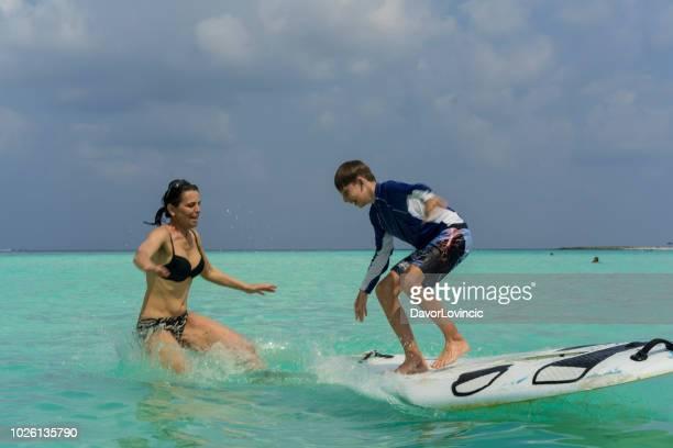 Mather and her son are balancing on surfboard against blue sky on sandy bikini beach on Gulhi island, Maldives