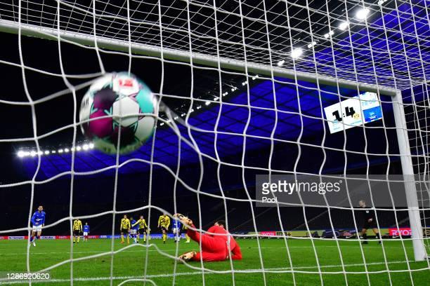 Matheus Cunha of Berlin scores his team's second goal with a penalty against goalkeeper Roman Buerki of Dortmund during the Bundesliga match between...