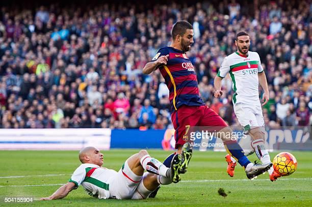 Matheus Doria of Granada CF tackles Arda Turan of FC Barcelona during the La Liga match between FC Barcelona and Granada CF at Camp Nou on January 9...