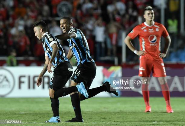 Matheus Henrique of Gremio celebrates with teammate after scoring the second goal of his team during a Group E match between America de Cali and...