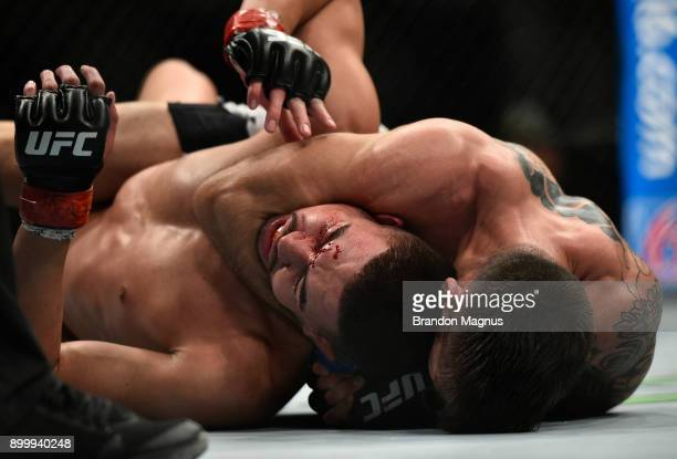 Matheus Nicolau of Brazil attempts to secure a choke submission against Louis Smolka in their flyweight bout during the UFC 219 event inside TMobile...