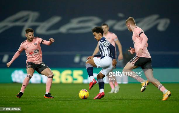 Matheus Pereira of West Bromwich Albion is challenged by Oliver Norwood and Oliver McBurnie of Sheffield United during the Premier League match...