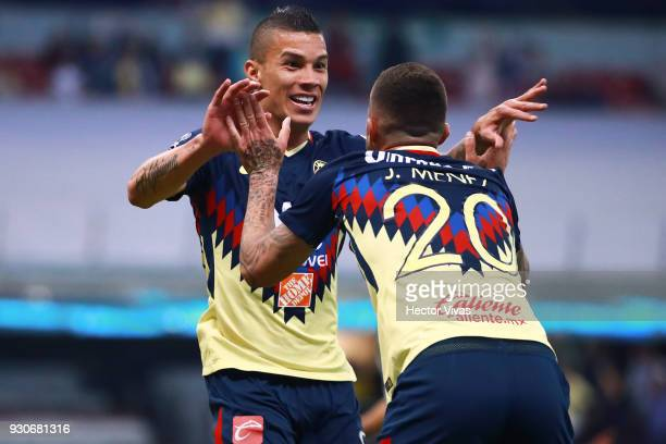 Matheus Uribe of America celebrates with teammates after scoring the first goal of his team during the 11th round match between America and Leon as...