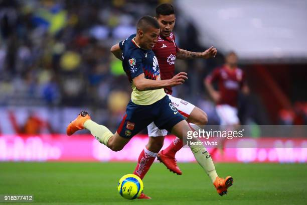 Matheus Uribe of America struggles for the ball with Sebastian Vegas of Morelia during the 7th round match between America and Monarcas as part of...