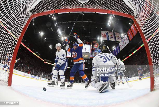 Mathew Barzal and Brock Nelson of the New York Islanders celebrate a power-play goal by Anthony Beauvillier against Frederik Andersen of the Toronto...