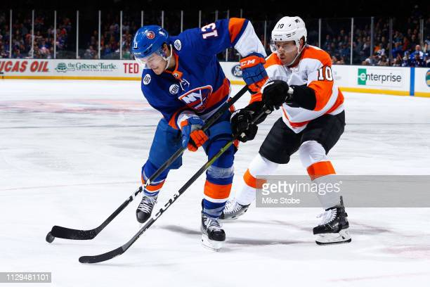 Mathew Barzal of the New York Islanders and Corban Knight of the Philadelphia Flyers battle for the puck at NYCB Live's Nassau Coliseum on March 9...