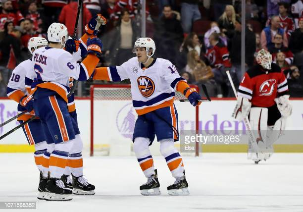 Mathew Barzal of the New York Islanders celebrates his game winning goal with teammates Anthony Beauvillier and Ryan Pulock in overtime as Keith...