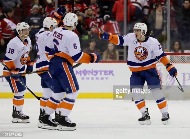 Mathew Barzal of the New York Islanders celebrates his game winning goal with teammates Nick Leddy and Ryan Pulock in overtime against the New Jersey...