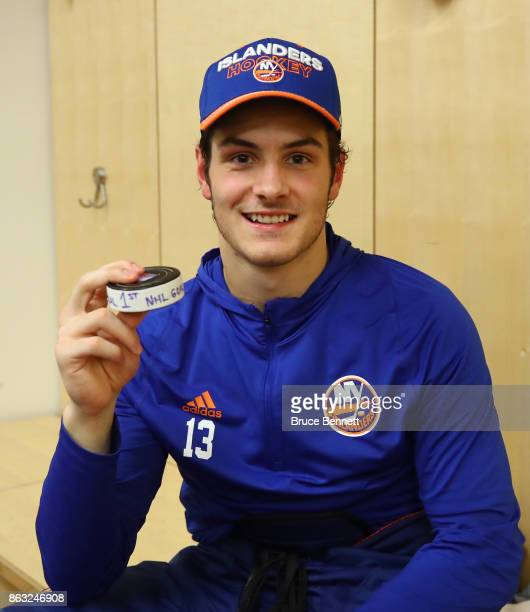 Mathew Barzal of the New York Islanders holds the puck with which he scored his first NHL goal against the New York Rangers at Madison Square Garden...