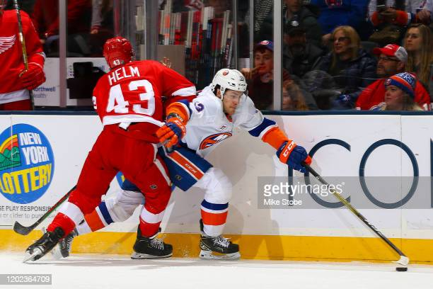 Mathew Barzal of the New York Islanders is checked by Darren Helm of the Detroit Red Wings during the first period at NYCB Live's Nassau Coliseum on...