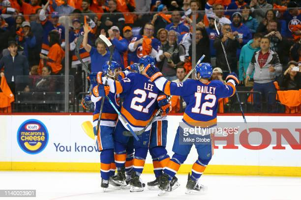 Mathew Barzal of the New York Islanders is congratulated by his teammates after scoring a first period goal against the Carolina Hurricanes in Game...