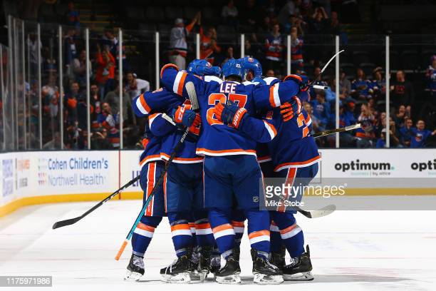 Mathew Barzal of the New York Islanders is congratulated by his teammates after scoring the game-tying goal with 27 seconds remaining in the third...