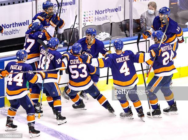 Mathew Barzal of the New York Islanders is congratulated by his teammates after scoring the game winning goal at 4:28 of overtime against the...