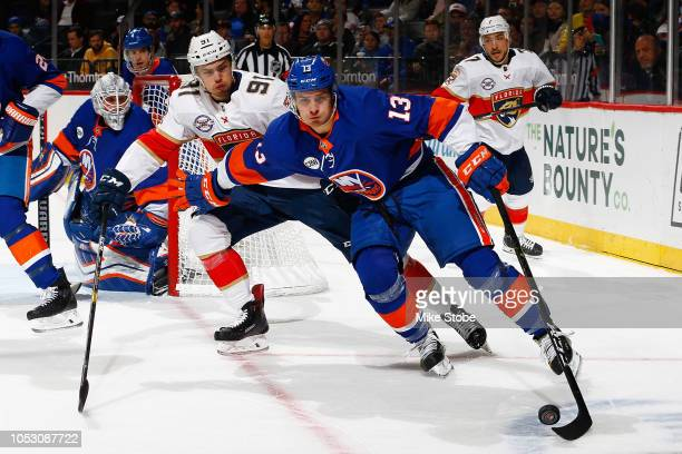 Mathew Barzal of the New York Islanders plays the puck against Juho Lammikko of the Florida Panthers at Barclays Center on October 24, 2018 the...