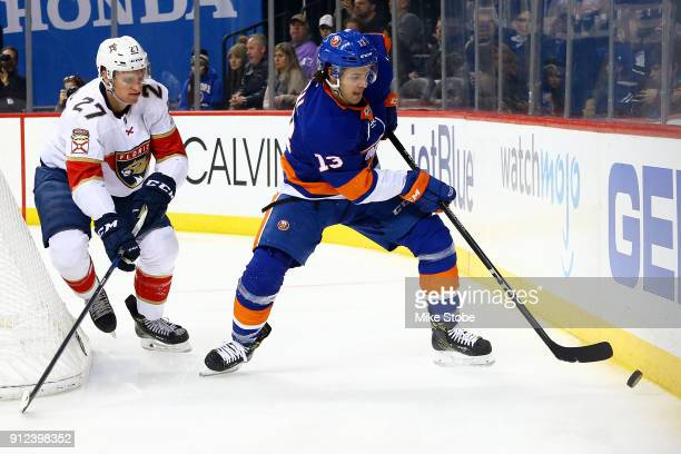 Mathew Barzal of the New York Islanders plays the puck behind the net amid pressure from Nick Bjugstad of the Florida Panthers during the second...