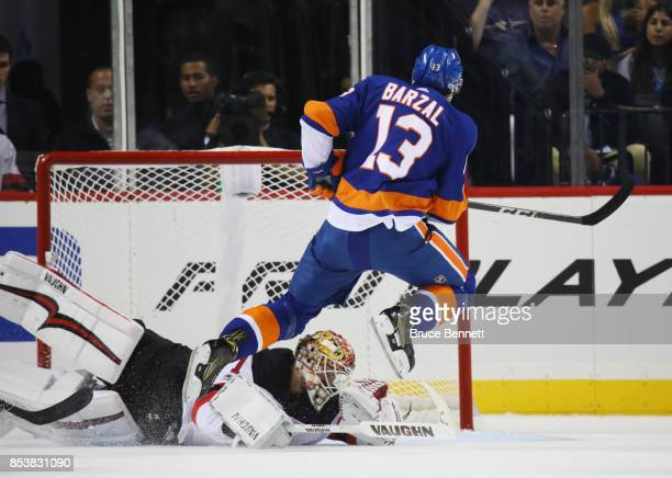 Mathew Barzal of the New York Islanders scores a powerplay goal at 1415 of the first period against Keith Kinkaid of the New Jersey Devils during a...