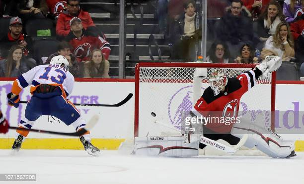 Mathew Barzal of the New York Islanders scores the game winning goal over Keith Kinkaid of the New Jersey Devils in overtime at Prudential Center on...