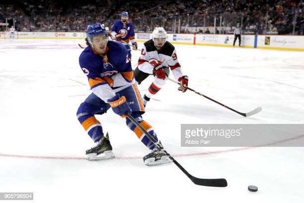 Mathew Barzal of the New York Islanders skates with the puck against Marcus Johansson of the New Jersey Devils in the first period during their game...