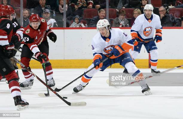 Mathew Barzal of the New York Islanders skates with the puck as Oliver EkmanLarsson and Clayton Keller of the Arizona Coyotes defend during the...