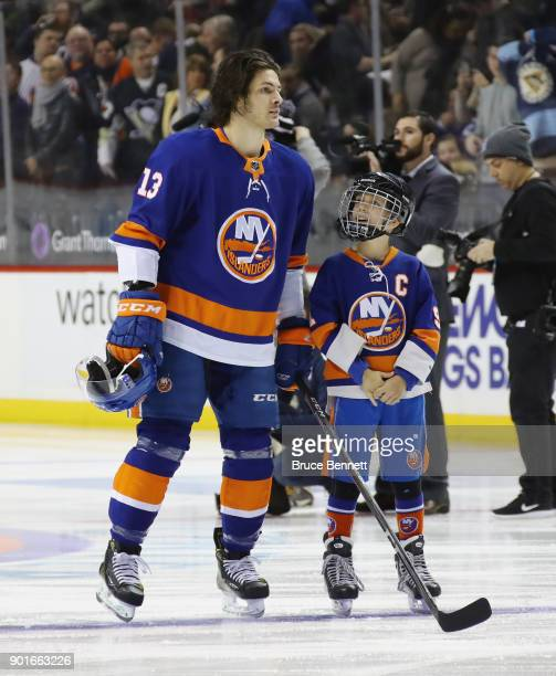 Mathew Barzal of the New York Islanders stands at attention with a youth hockey player during the national anthem prior to the game against the...