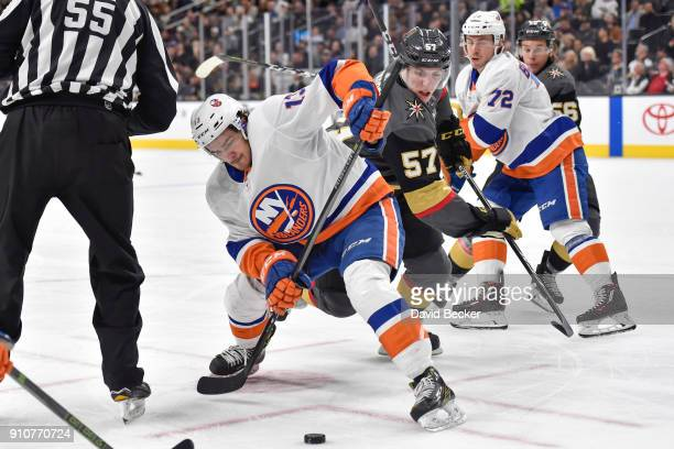 Mathew Barzal of the New York Islanders takes a faceoff against David Perron of the Vegas Golden Knights during the game at TMobile Arena on January...