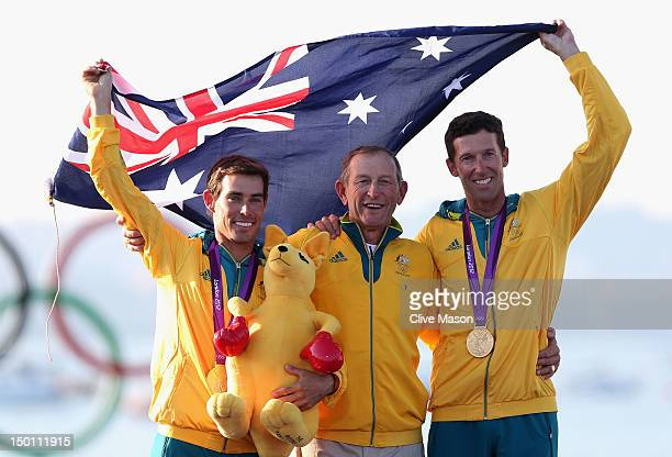 Mathew Belcher and Malcolm Page of Australia celebrate with Australian Sailing Team Head Coach Victor Kovalenko after winning gold in the Men's 470...