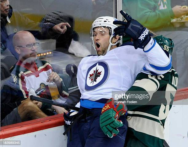 Mathew Dumba of the Minnesota Wild checks Eric Tangradi of the Winnipeg Jets into the boards during the first period of the game on October 10 2013...