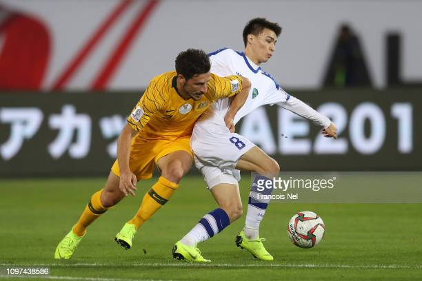 Mathew Leckie of Australia battles for possession with Ikromjon Alibaev of Uzbekistan during the AFC Asian Cup round of 16 match between Australia...