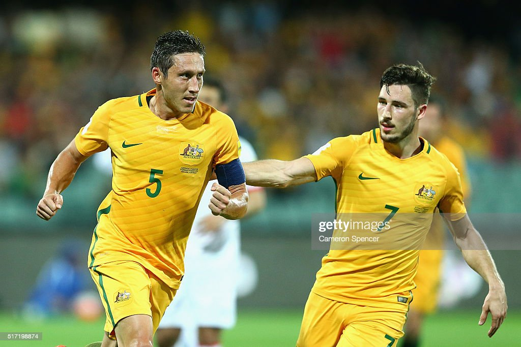 Mathew Leckie of Australia congratulates team mate Mark Milligan of Australia after kicking a penalty goal during the 2018 FIFA World Cup Qualification match between the Australia Socceroos and Tajikistan at the Adelaide Oval on March 24, 2016 in Adelaide, Australia.