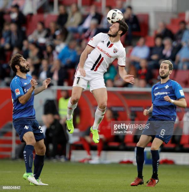 Mathew Leckie of Ingolstadt jumps for the ball between Hamit Altintop and Mario Vrancic of Darmstadt during the Bundesliga match between FC...