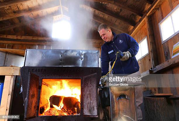 Mathew Noiseux uses a digital thermometer to check on the boiling maple water in the sugar shack where maple sugaring takes place at the Moose Hill...