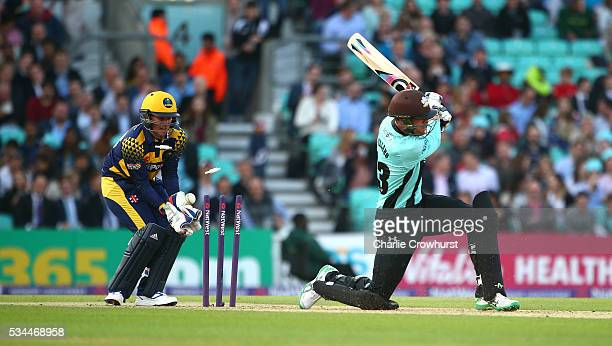 Mathew Pillans of Surrey is bowled out while Chris Cooke of Glamorgan looks on during the Natwest T20 Blast match between Surrey and Glamorgan at The...