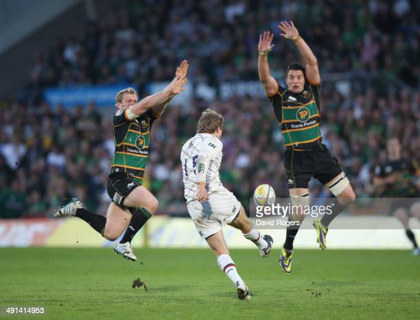 Mathew Tait of Leicester kicks the ball past Mike Haywod and Phil Dowson during the Aviva Premiership semi final match between Northampton Saints and...