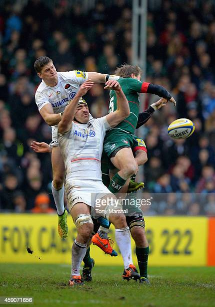 Mathew Tait of Leicester Tigers jumps for a high ball with David Strettle and Kelly Brown of Saracens during the Aviva Premiership match between...