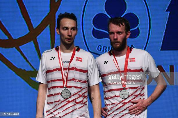Mathias Boe and Carsten Mogensen of Denmark celebrate on the podium during Men's Double medals ceremony of the BCA Indonesia Open 2017 at Plenary...