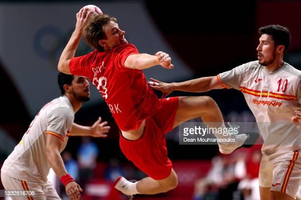 Mathias Gidsel of Team Denmark shoots at goal while under pressure from Alex Dujshebaev Dovichebaeva of Team Spain during the Men's Semifinal...