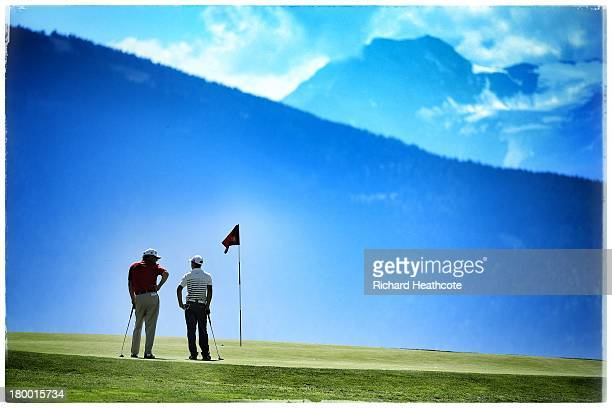Mathias Gronberg of Sweden talks with 13yr old amateur Ye WoCheng of China on the 7th green during the first round of the Omega European Masters at...
