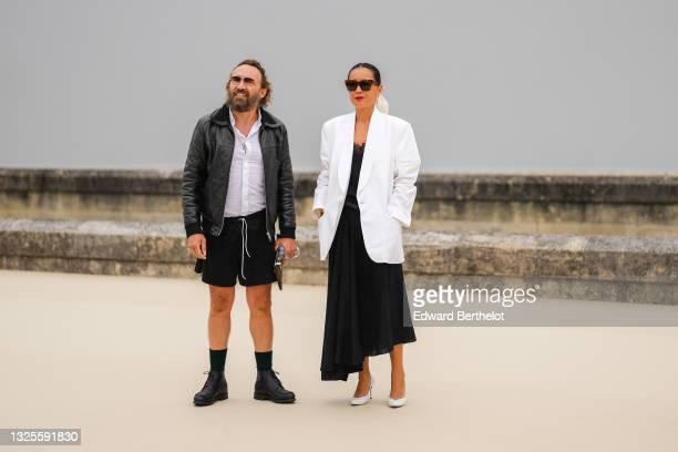 Mathias Kiss wears black sunglasses, a gold pendant necklace, a white shirt, a black shiny leather jacket, black sport shorts, a brown suede clutch,...