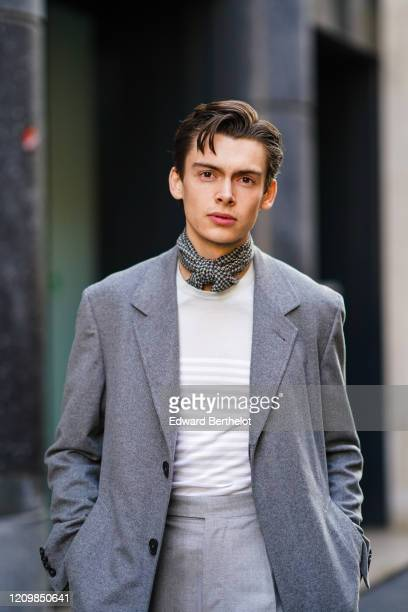 Mathias Le Fevre wears a black and white houndstooth scarf, a light grey top with white stripes, a grey coat, grey pleated pants, during Paris...