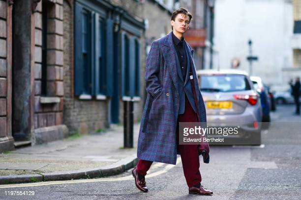 Mathias Le Fevre wears a navy blue shirt a blue checked long coat a blue jacket burgundy pants leather shoes during London Fashion Week Men's January...
