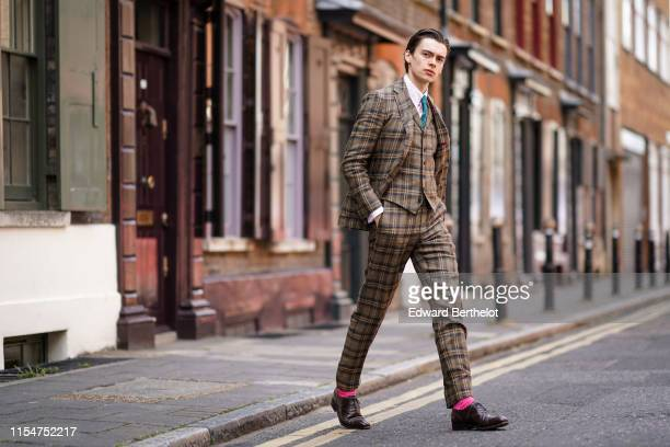 Mathias Lefevre wears a 3 piece suit a brown checked blazer jacket a shirt a green tie checked pants leather shoes pink socks during London Fashion...