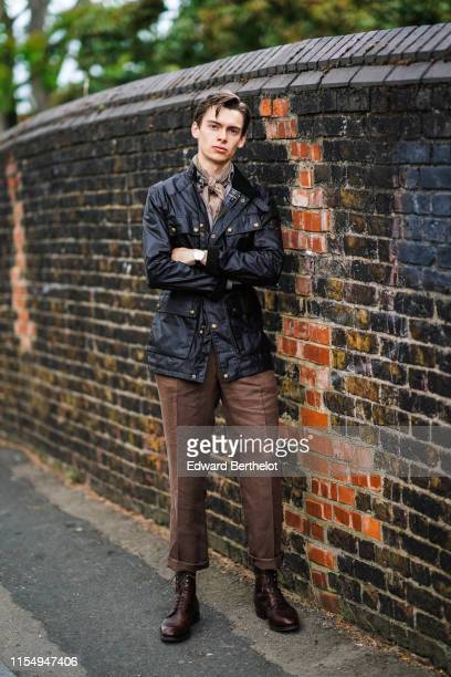 Mathias Lefevre wears a dark leather jacket a scarf brown pants brown leather shoes during London Fashion Week Men's June 2019 on June 09 2019 in...