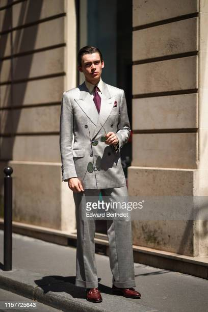 Mathias Lefevre wears a gray silver blazer jacket, flare pants, leather shoes, a white shirt, a tie, outside Thom Browne, during Paris Fashion Week -...