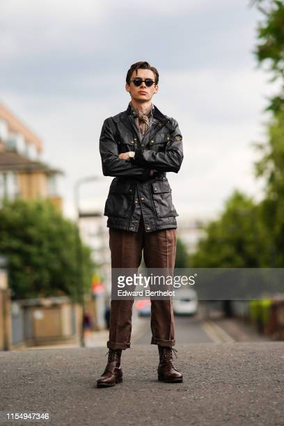 Mathias Lefevre wears sunglasses a dark leather jacket a scarf brown pants brown leather shoes during London Fashion Week Men's June 2019 on June 09...