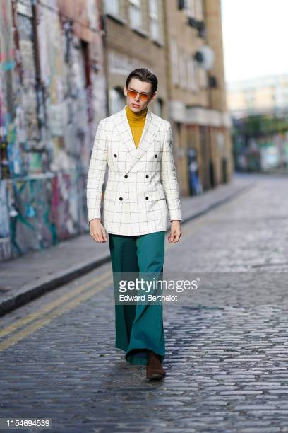Mathias Lefevre wears sunglasses a yellow turtleneck top a white checked blazer jacket green flare pants brown shoes during London Fashion Week Men's...