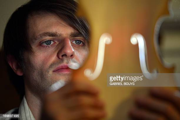 Mathias Menanteau a French violin maker looks at the fholes of a violin on February 1 2013 in his workshop in Rome After studying and working in...