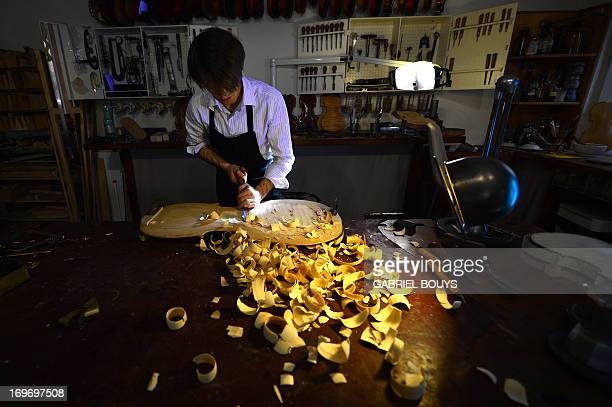 Mathias Menanteau a French violin maker works on a violin scroll on January 30 2013 in his workshop in Rome After studying and working in England and...