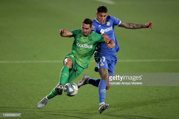 Mathias Olivera of Getafe and Joseba Zaldua of Real Sociedad compete for the ball during the Liga match between Getafe CF and Real Sociedad at...